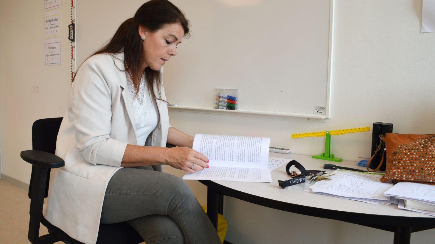 Jeanette Lindell, speciallärare och förstelärare på Rönnenskolan i Malmö bläddrar i uppsatsen hon varit med och skrivit om pysparagrafen.