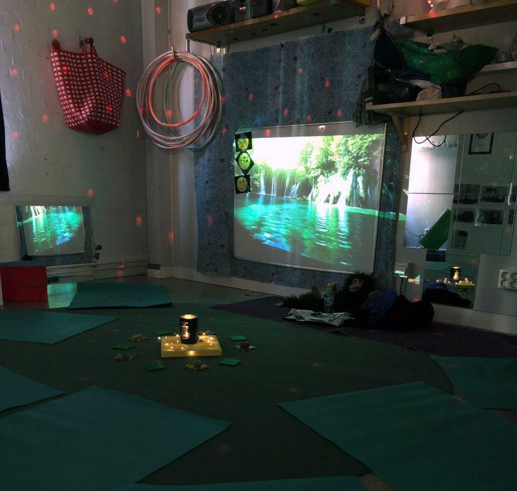 Stämningsskapande ljus, projektioner på väggen och mattor på golvet då förskolan ska ha sagoyoga.