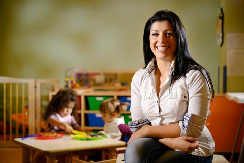 Kvinna sitter på stol framför lekande barn.