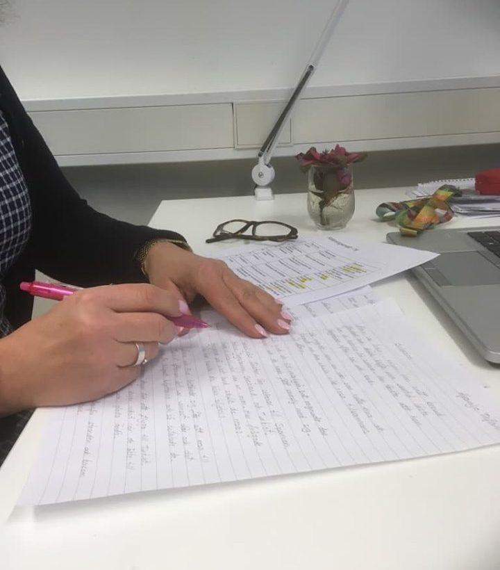 Kvinna skriver på textblad.