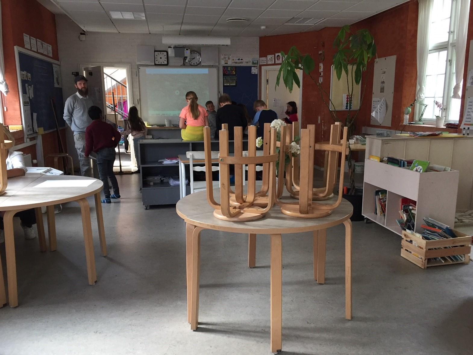 Klassrum där pallar står uppe på bänkarna.