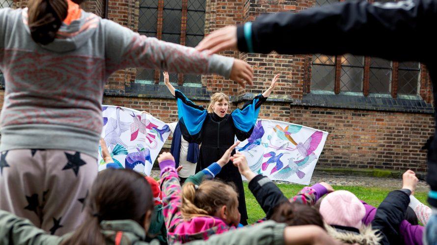 Barn från Stenkulaskolan tittar på vandringsteater vid Petrikyrkan.