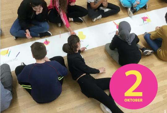Elever målar på papper som ringlar sig fram på golvet.