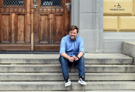 Johan Ahx sitter på trappan framför den gamla ingången till Malmö Latinskola.