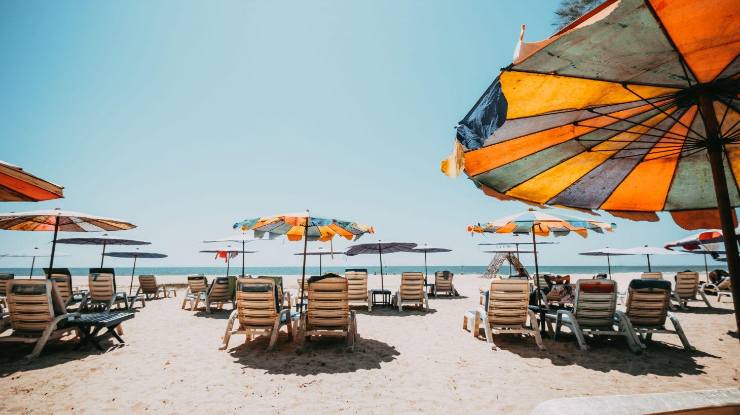 Solstolar och parasoller på en strand.