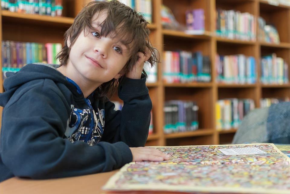 Barn sitter i bibliotek och läser i bok.