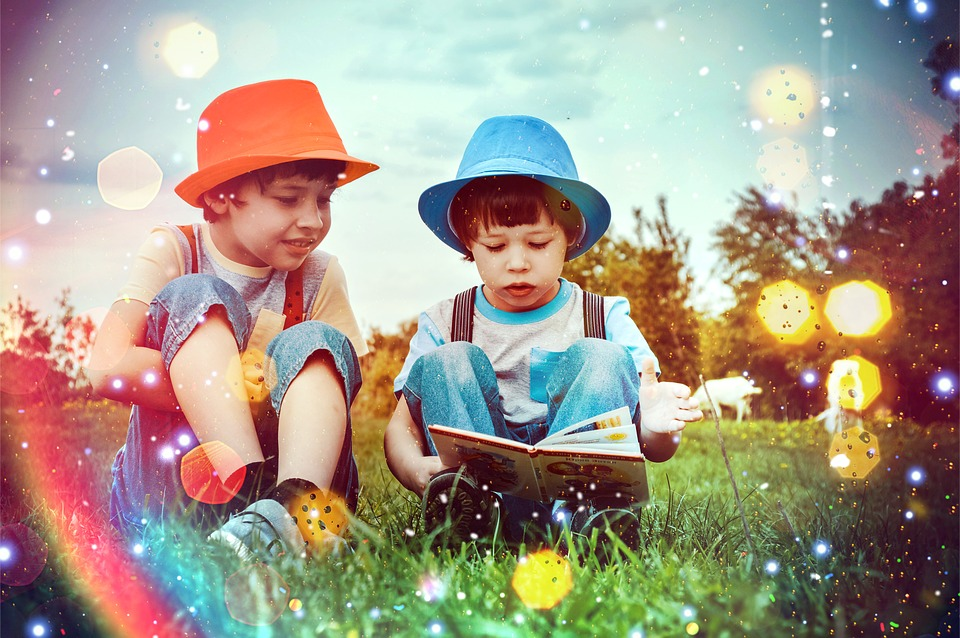 Tv barn sitter och läser på sommaräng.