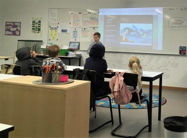 Elev redovisar framför projicerad presentation.