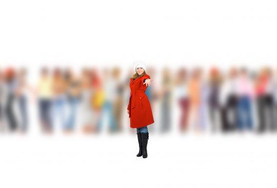 Kvinna i röd kappa sträcker ut handen. Bakom henne står flera människor som är suddiga.