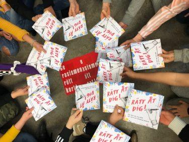 """Barn sträcker fram sina händer över ett rött kort där det står """"Ge rasismen rött kort"""""""
