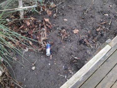 En blå och metallfärgade burk ligger slängd på marken.