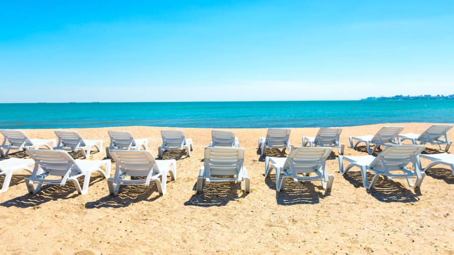 Solstolar på sandstrand vända mot turkost hav.