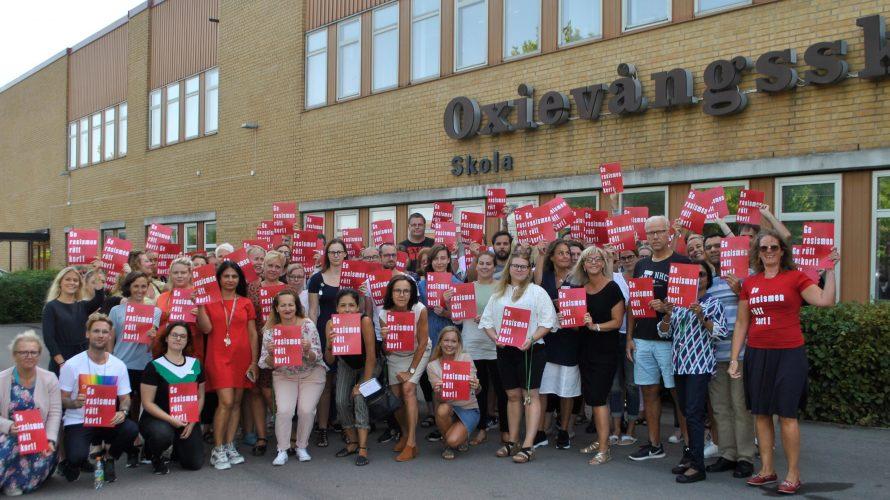 """Personalen på Oxievångsskolan står framför skolan och håller upp ett rött kort som det står """"Ger rasismen rött kort"""" på."""