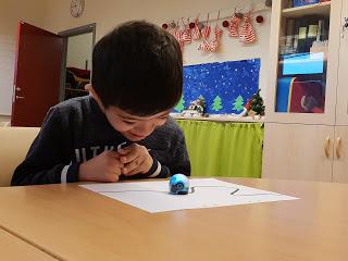 Eleven Allan Khan sitter vid ett bord och arbetar med en ozobot.