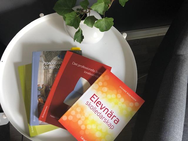 Fyra böcker ligger i hög på bord.