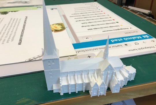 Liten vit modell över kyrka.