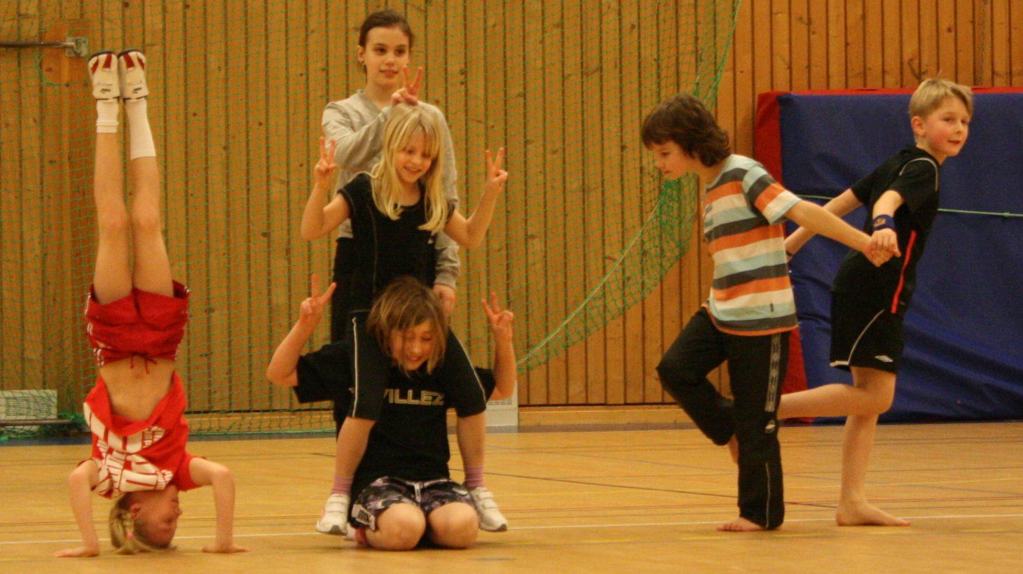 Sex barn gör rörelser i gymnastiksal.