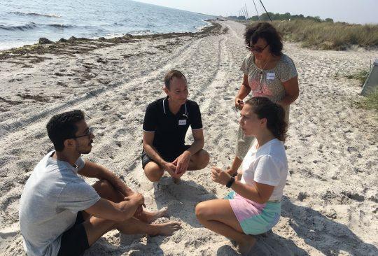 Fyra personer samtalar på en strand