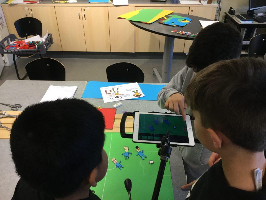 Tre elever filmar med ipad.