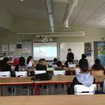 Elever i klassrum framför projicerad presentation.