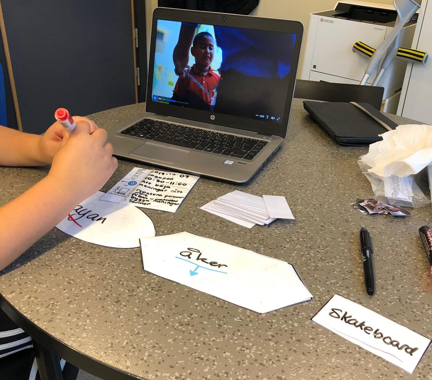 Uppslagen dator där ett barn sitter och tittar med skrivna lappar framför sig.