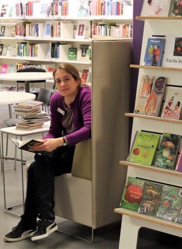 Kvinna sitter i läsfåtölj i bibliotek.