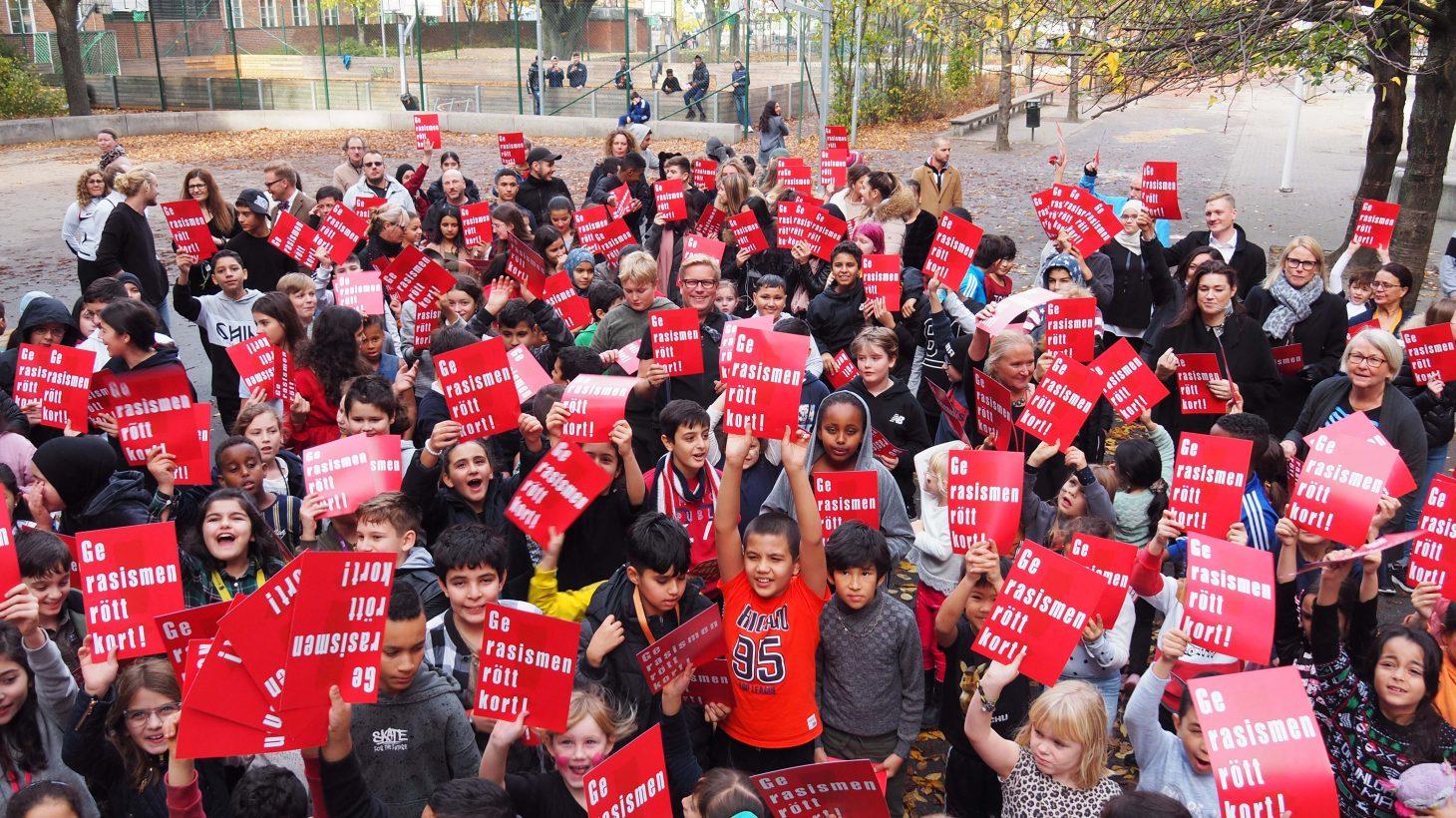 """Elever och personal på Johannesskolan håller upp lappar med texten """"Ge rasismen rött kort""""."""