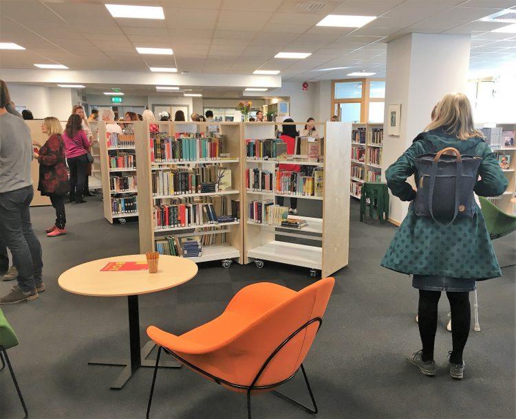 Fullt av folk bland bibliotekens hyllor.