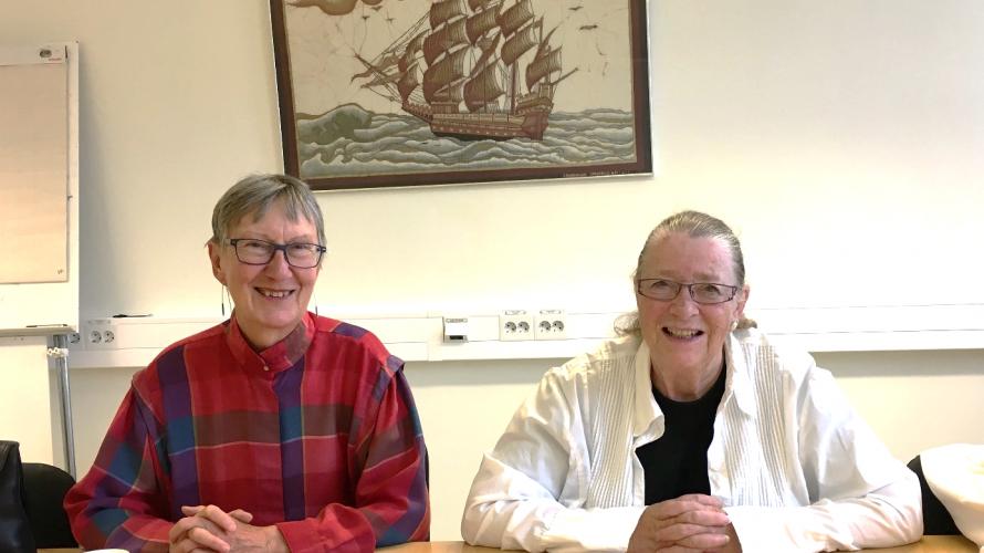 Två kvinnor ler in i kamera.