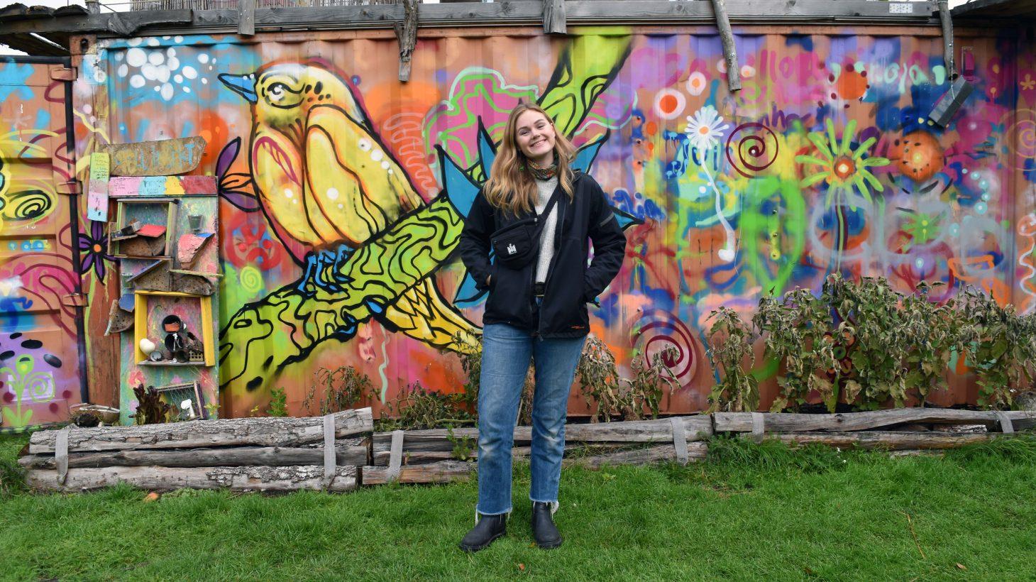 Kvinna framför grafittivägg.