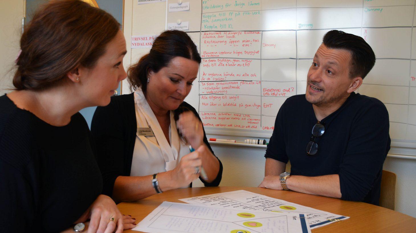 Skolledning sitter vid ett bord där papper med KL-strukturer presenteras.