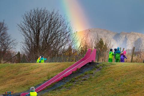 Regnbåge slutar vid rutschkana där barn leker.