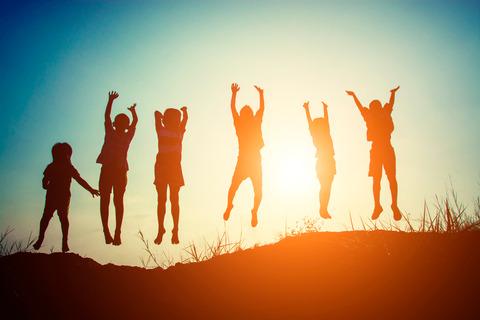 Barn som hoppar i motljus vid strand.