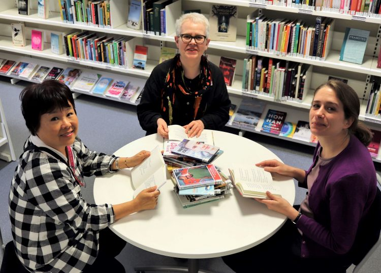 Tre kvinnor sitter runt bord med massor av böcker framför sig.