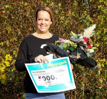 Elin Strömgren med vinnarcheck och blommor