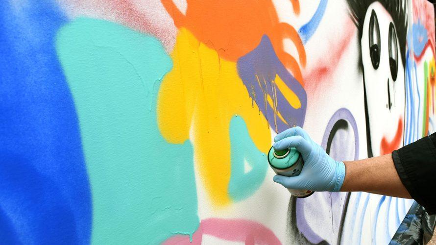 Hand som sprayar färg på vägg med burk.