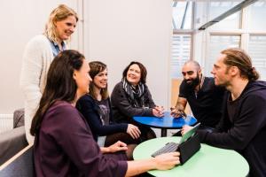 Pedagoger och rektorer sitter vid runda bord.