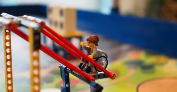 Legogubbe i rullstol pekar uppåt.