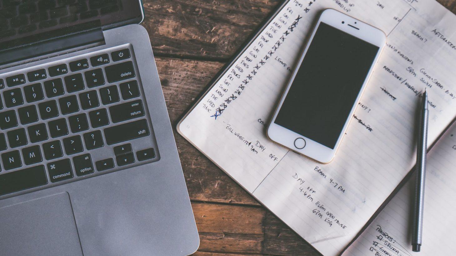 Dator, mobil och almanacka ligger uppslaget på bord.