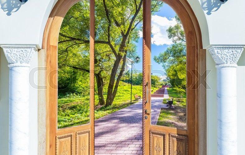 Pardörr öppnas ut mot skog och stenlagd gång.