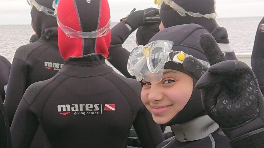 Elever i våtdräkt och snorkel gör v-tecken.