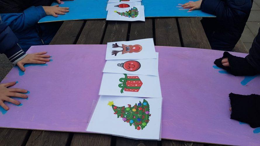 Barns händer hålls på papper med julsymboler i mitten.