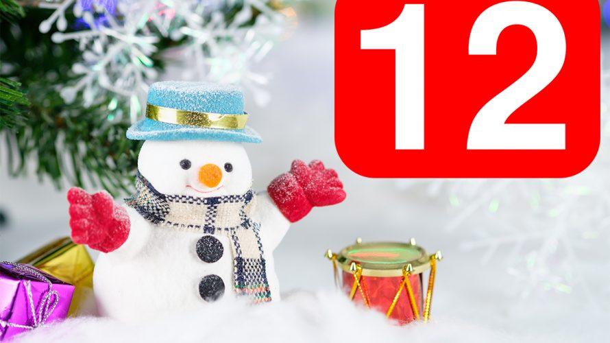 En tomte ståendes i snö och siffran 12.