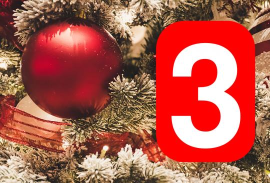 Röd julkula hänger i gran och siffran tre.