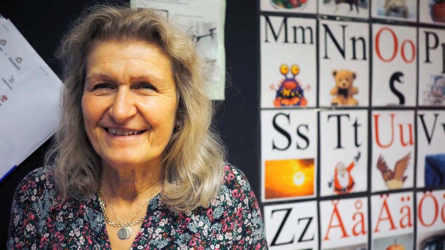 Mariann Mattsson står framför en svart tavla som har ett alfabet uppsatt. Lärare på Johannesskolan.