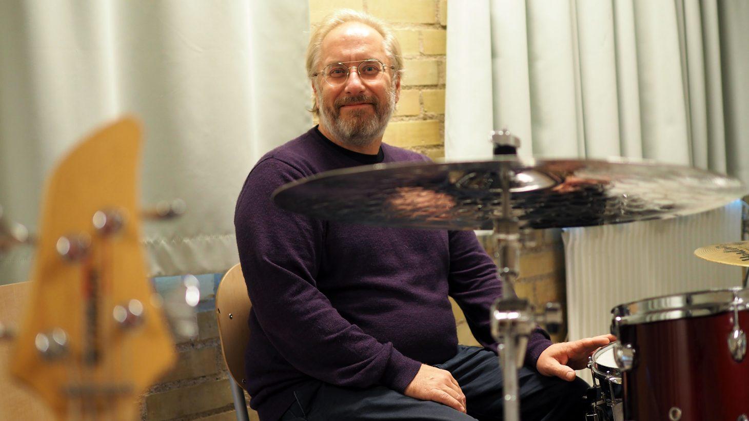 Rikard Persson sitter framför ett trumset med en bas i förgrunden