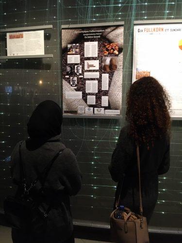 Två elever står och tittar på affisch.