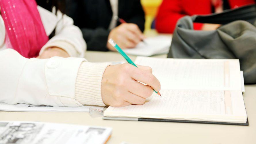 En hand som skriver i en anteckningsbok.