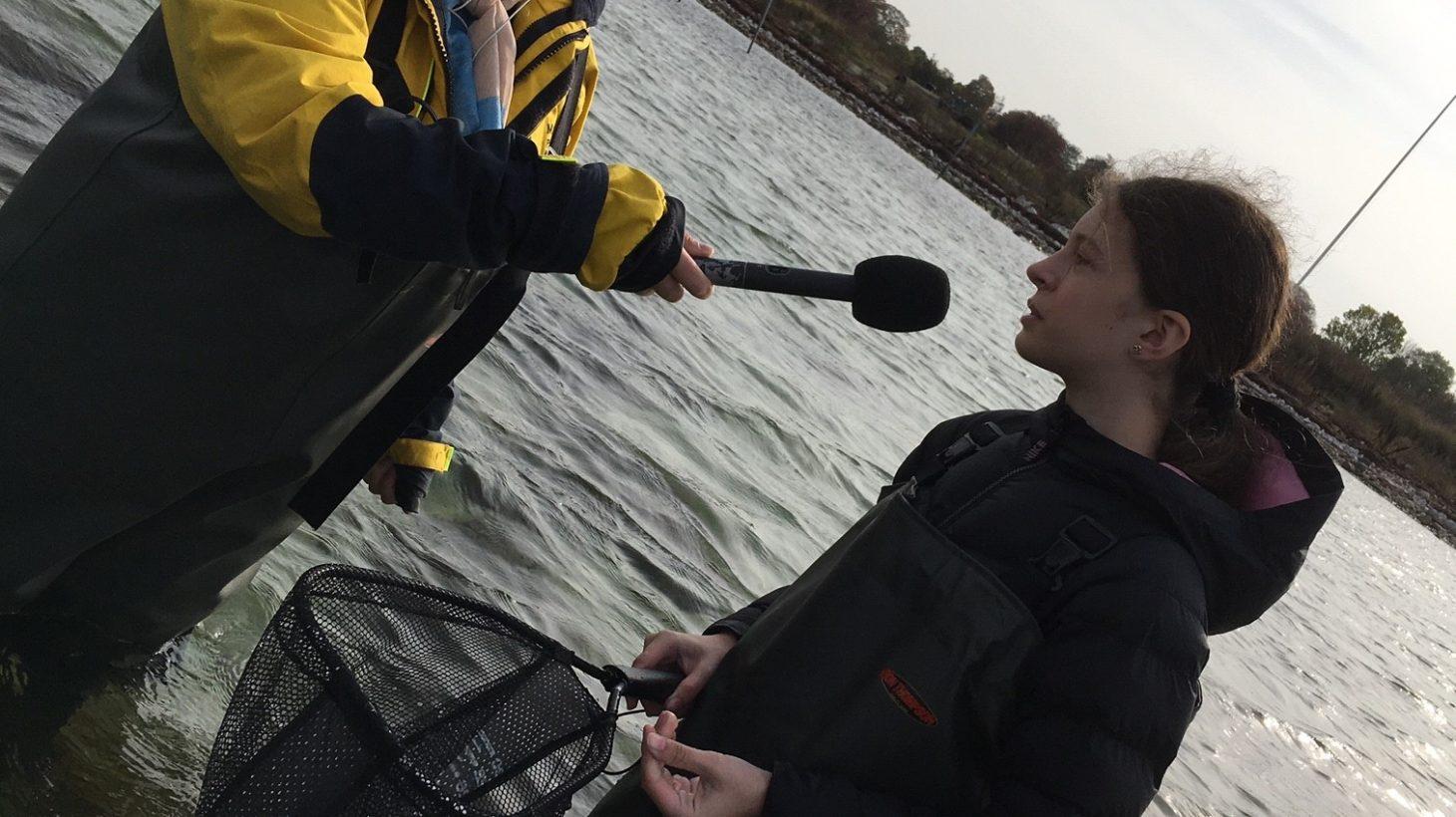 Journalist intervjuar elev som står i havet med vadarbyxor och håv.