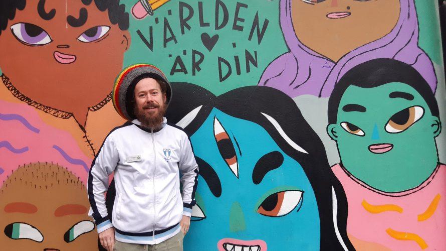 """Alexander Tandefelt, förstelärare på Lindängeskolan, står framför en vägg med en målning med olika ansikten och texten """"Världen är din""""."""
